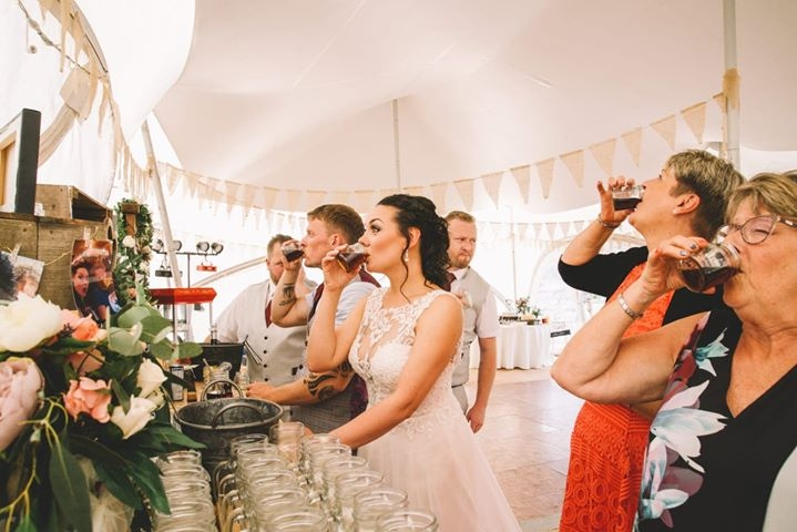 Bride and guests getting stuck into drinks inside the marquee