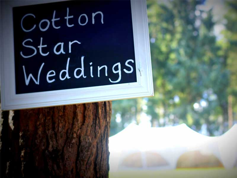 """Chalk sign in the foreground """"Cotton Star Weddings"""" marquee in the background out of focus"""